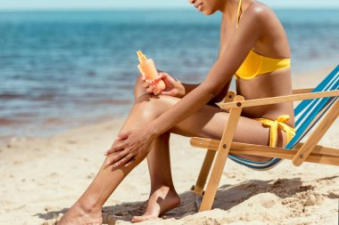 cropped image of woman applying sunscreen lotion on skin while sitting on deck chair on sandy beach