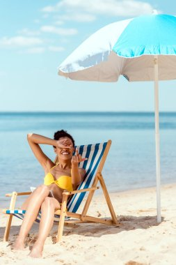 Young woman covering eyes by hand and showing middle finger while laying on deck chair under beach umbrella in front of sea stock vector