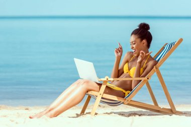 Smiling african american woman gesturing by fingers and communicating by laptop while sitting on deck chair on sandy beach stock vector