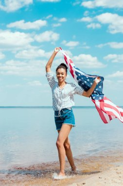 Smiling african american woman running in sea water with american flag, independence day concept stock vector