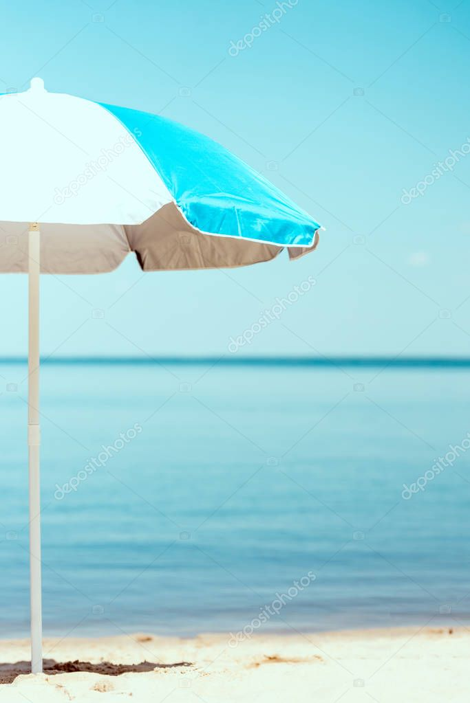 selective focus of beach umbrella in front of sea
