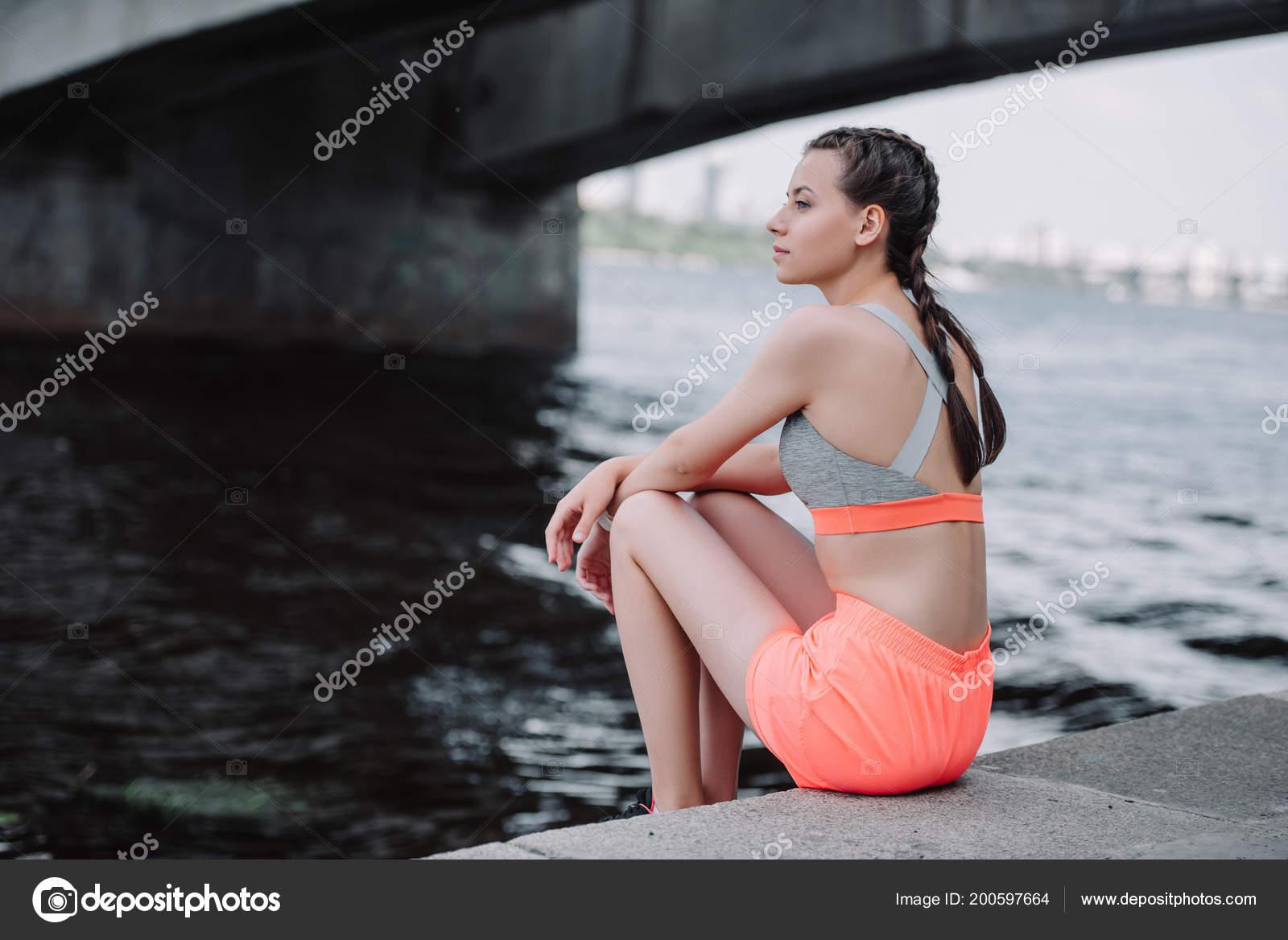 3f7179ab868 Ελκυστική Νεαρή Γυναίκα Αθλητικό Αθλητικά Ενδύματα Που Κάθεται Στην  Αποβάθρα– εικόνα αρχείου