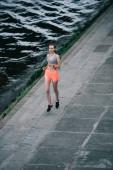 Fotografia giovane sportiva jogging sulla banchina vicino fiume