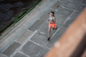 Fotografie overhead view of young sportswoman running in city