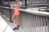 Fotografie verkürzten Blick auf sportliche Frau hält Sportflasche, Blick auf Uhr und am Geländer stehen