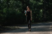 athletic girl holding sports bottle with water and walking in park