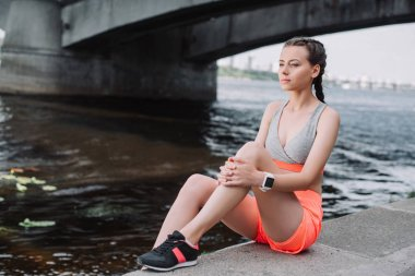 attractive sportswoman in sneakers sitting on quay near river