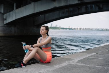 beautiful sportswoman with smartwatch and sports bottle sitting on quay near river