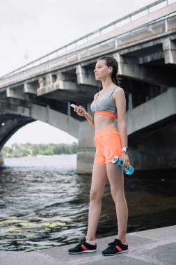 young sportswoman holding smartphone, earphones and sports bottle