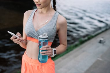 cropped view of young sportswoman holding smartphone with earphones and sports bottle with water