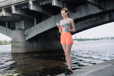 young sportswoman holding smartphone and bottle with water