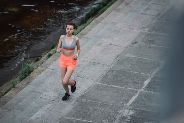 young athletic woman running on quay