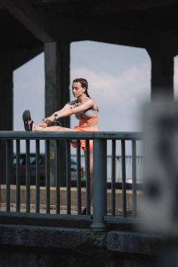 beautiful sportive woman stretching leg on railings on bridge