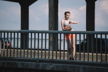 young sportswoman with smartphone looking at watch and standing on bridge