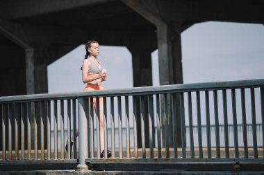 sportswoman jogging and listening music on bridge in city