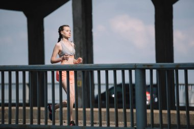 female jogger listening music and running on bridge in city