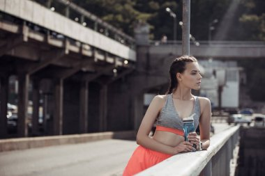attractive sportswoman holding sports bottle with water in city