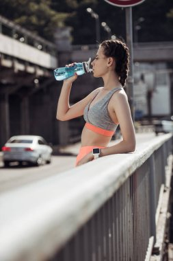 athletic sportswoman with smart watch drinking water in city