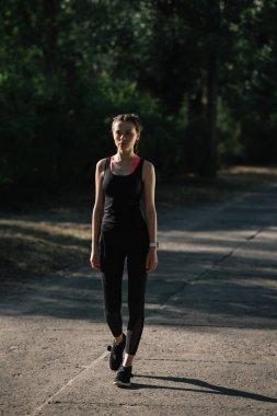 athletic woman in sportswear walking on path in park