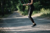 Fotografie cropped view of athletic woman training with skipping rope on path in park