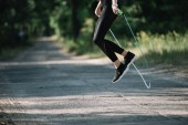 Fotografie cropped view of sportswoman jumping on skipping rope in park