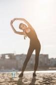 Fényképek attractive sportswoman stretching on beach with sports bottle