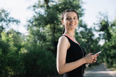 beautiful smiling sportswoman listening music with earphones and smartphone