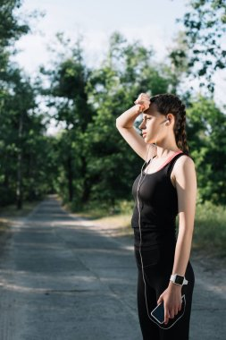 tired athletic woman earphones, smart watch and smartphone