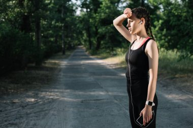 beautiful tired sportswoman listening music with earphones and smartphone