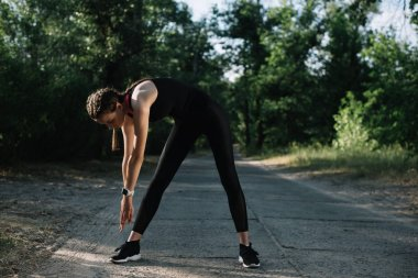 young athletic woman exercising on path in park
