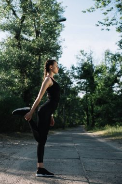 attractive sportswoman exercising and stretching leg on path in park
