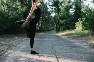 cropped view of sportswoman stretching leg on road in park