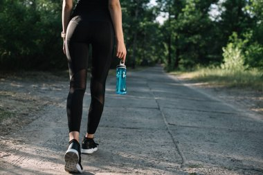 cropped view of sportswoman with sports bottle of water walking on path