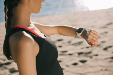 cropped view of woman looking at smart watch