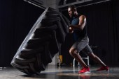Fotografie side view of athletic african american man exercising with tyre and looking away in gym