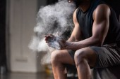 Oříznout záběr svalové africké americké sportovce použití talku na rukou