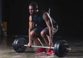 focused muscular african american sportsman lifting barbell and looking away in gym