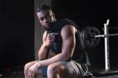 africké americké sportovce s ručníkem na rameni sedí po tréninku v tělocvičně