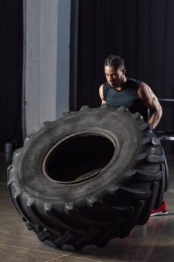 handsome muscular young african american sportsman training with tire