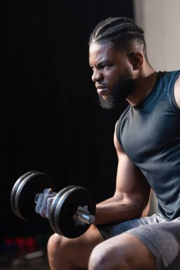 serious african american sportsman exercising with dumbbell and looking away
