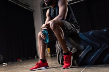 cropped shot of young african american sportsman sitting  tyre and holding bottle of water in gym