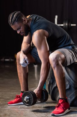 athletic african american man sitting on tyre and exercising with dumbbell