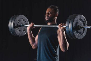 muscular african american sportsman lifting barbell on black