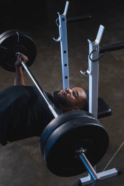 high angle view of muscular african american man lifting barbell in gym