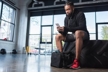 handsome african american man in earphones sitting in tyre and using smartphone in gym