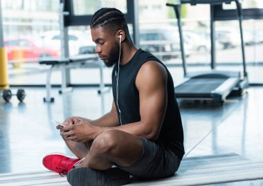 side view of muscular african american man in earphones using smartphone while sitting on yoga mat in gym