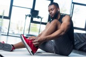 Fotografie low angle view of young african american sportsman tying shoelaces in gym