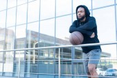 Fotografie pensive african american man in earphones leaning at railings with basketball ball and looking away