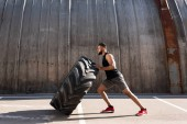 Photo side view of muscular african american sportsman exercising with tire on street