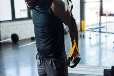 cropped shot of muscular young african american man training with fitness straps in gym